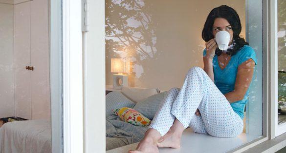 woman in pajamas drinking coffee from window